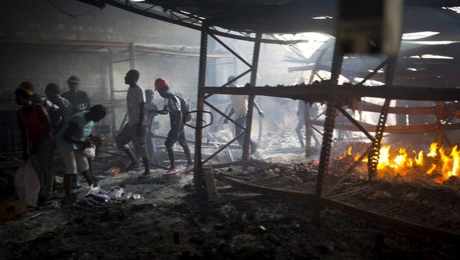 People loot a Delimart store that was burned during two days of protests against a planned hike in fuel price in Port-au-Prince, Haiti, Sunday, July 8, 2018. Government officials had agreed to reduce subsidies for fuel as part of an assistance package with the International Monetary Fund, but the government suspended the fuel hike after widespread violence broke out.