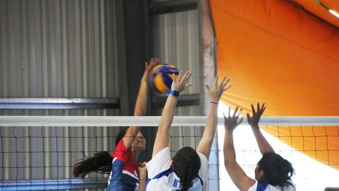 In this file photo from the Micronesian Games in Yap  this summer, Lori Okada goes over and through the Marshall Islands' block during women's volleyball action. Guam's volleyball teams now set the Pacific Games and Samoa in their sights.