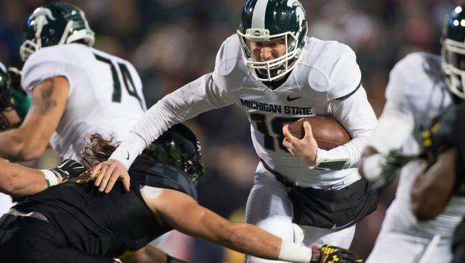 Michigan State Spartans quarterback Connor Cook (18) runs past Maryland Terrapins defensive lineman Darius Kilgo (97) during the first quarter at Byrd Stadium.