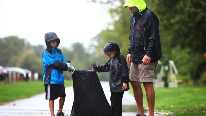 From left, Andrew, 7, Avery, 5, and dad, Ryan Howe, all of Rochester, carry a trash bag filled with litter found at Durand-Eastman beach as part of the annual International Coastal Cleanup on Saturday.