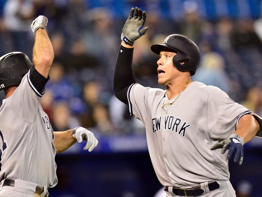 New York Yankees' Aaron Judge, right, celebrates his home run with Brett Gardner (11) against the Toronto Blue Jays during the 13th inning of a baseball game Wednesday, June 6, 2018, in Toronto.