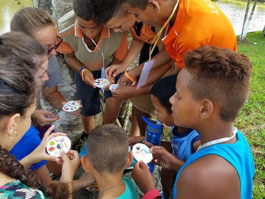 Teens from Christ Community Church in Montreat play a card game with Cuban children at a kid's camp during a 10-day mission trip to the country in July.