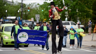 Ron Valentine juggles along Midland Ave. during Garfield's 100th anniversary parade on Sunday, April 30, 2017.