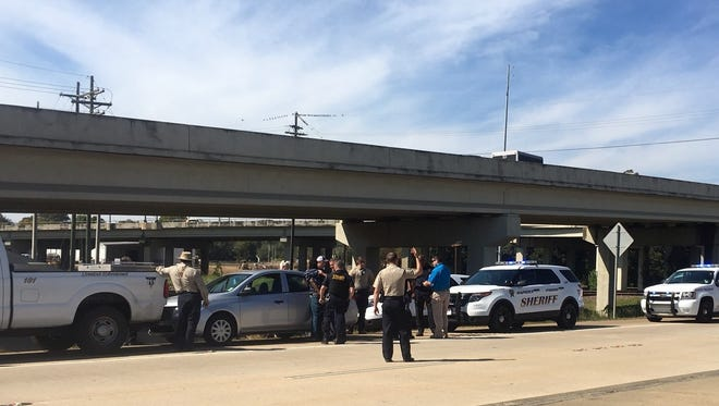 Law enforcement officers stand on Interstate 49 in Alexandria on Tuesday with armed robbery suspect Eric Cleveland, who led them on a chase from Grant Parish.