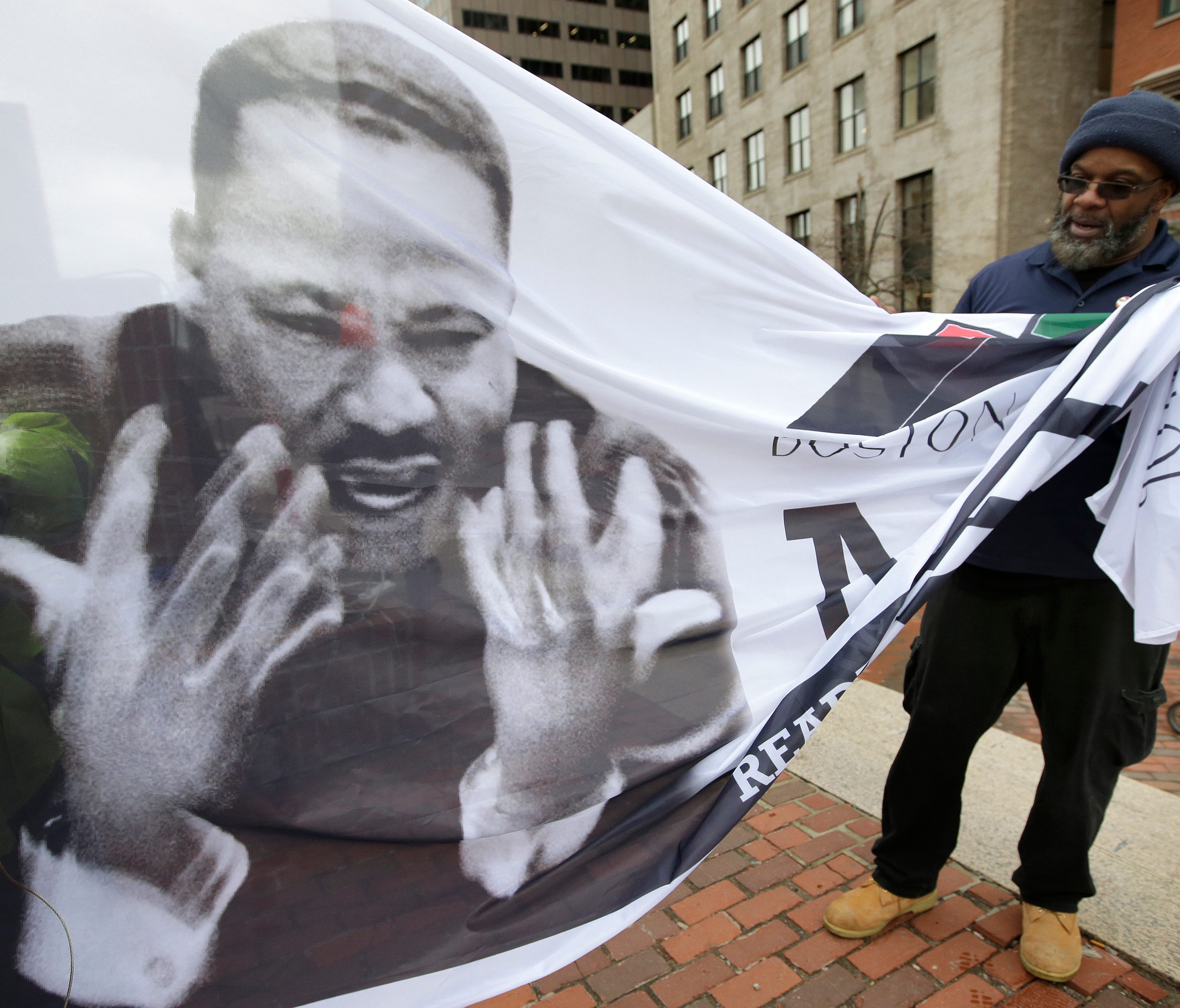 Steve Coachman, of Boston, right, unfurls a flag featuring a likeness of Martin Luther King Jr. on April 2, 2018 before a remembrance ceremony on City Hall Plaza in Boston. Dozens of speakers aged 5 to 91 took turns reading short passages from King's