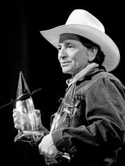 A clean-shaven Willie Nelson accepts the Vocal Duo