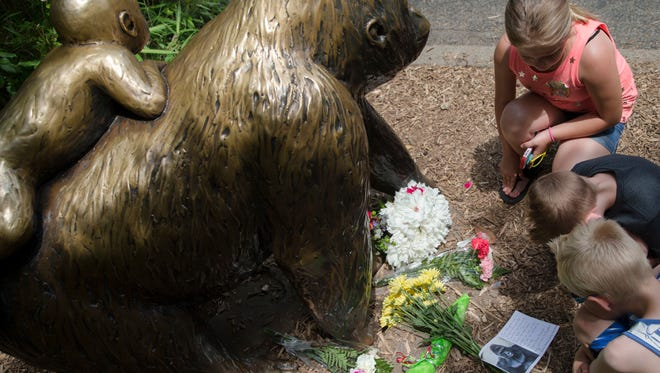 Children pause at the feet of a gorilla statue where flowers and a sympathy card have been placed, outside the Gorilla World exhibit at the Cincinnati Zoo & Botanical Garden, Sunday, May 29, 2016, in Cincinnati. On Saturday, a special zoo response team shot and killed Harambe, a 17-year-old gorilla, that grabbed and dragged a 4-year-old boy who fell into the gorilla exhibit moat. Authorities said the boy is expected to recover. He was taken to Cincinnati Children's Hospital Medical Center.