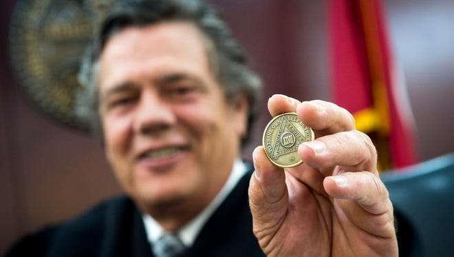 Judge Gale Robinson poses with his 27-year sobriety coin from a 12-step fellowship in his courtroom at the Judge AA Birch Building, Wednesday, Aug. 10, 2016, in Nashville, Tenn. Judge Robinson typically carries his sobriety coin in his pocket, sometimes taking it out to show defendants.