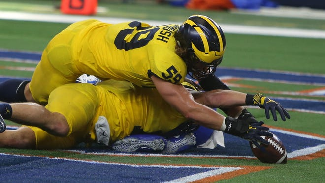 Michigan's Chase Winovich (bottom) forces a fumble in the end zone by Florida's Malik Zaire, as teammate Noah Furbush (59) recovers the ball for a touchdown in the fourth quarter of U-M's 33-17 win Saturday, Sept. 2, 2017, in Arlington, Texas.