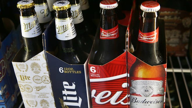 Bottles of Miller Lite and Budweiser are seen in Miami on Sept. 16, 2015. Budweiser is owned by Anheuser-Busch InBev and Miller Lite is owned by SABMiller. The two companies reached a $107 billion deal on Wednesday, Nov. 11, 2015.