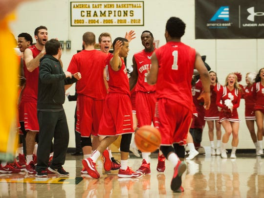 Stony Brook celebrates its 79-77 win over Vermont in the America East semifinal men's basketball game at Patrick Gym on Sunday.