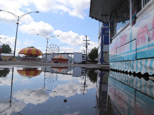 Rain puddles populate the midway of the Richland County Fair grounds on Saturday.