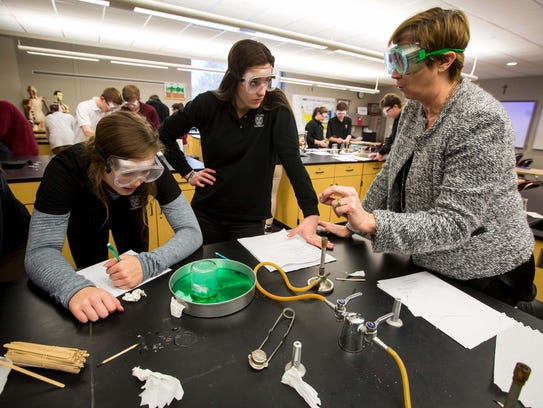 Clark, center, listens to Peg Conlon with her lab partners