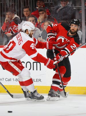 Devils defenseman Kyle Quincey shoots the puck away from Red Wings forward Henrik Zetterberg during the first period Friday in Newark, N.J.