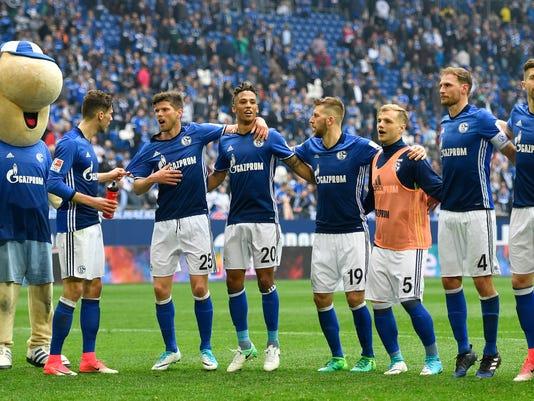 Schalke player celebrate the 1-1 with fans after the German Bundesliga soccer match between FC Schalke 04 and Borussia Dortmund in Gelsenkirchen, Germany, Saturday, April 1, 2017. (AP Photo/Martin Meissner)