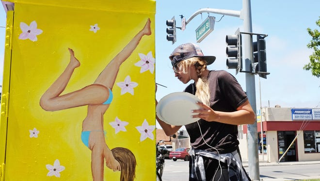 """Artist Gina Roman at work on """"Cali Girls,"""" a Salinas Urban Art Project at the corner of of E. Alisal St and N. Hebbron Avenue in Salinas."""