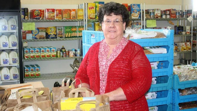Active Faith Executive Director Maryann Mihalic poses in the organization's storage room on her last day of work.