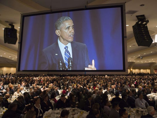 President Obama appears on a screen as he speaks during