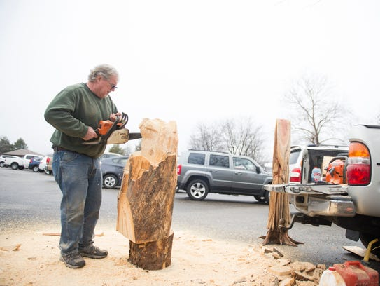 Jake Albright uses a chainsaw to shape a piece of wood
