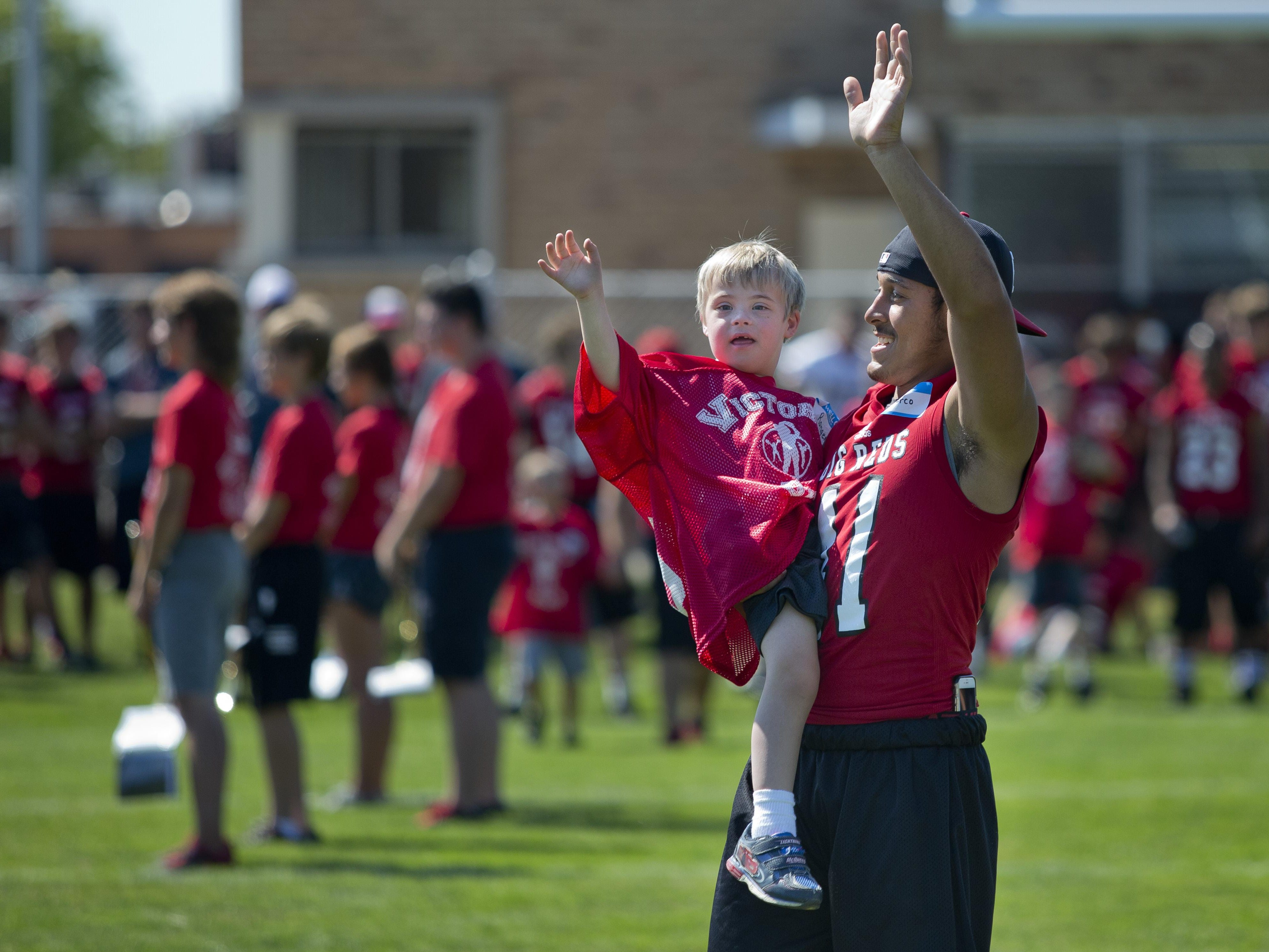 Marco Bolar carries Ranger Hopp as they wave to the audience during Victory Day Saturday, August 15, 2015 in Memorial Stadium at Port Huron High School. The event paired special needs students with mentors from the football and cheerleading teams.