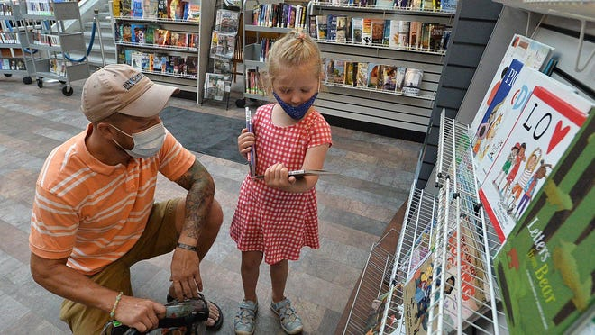 Josh Nickerson, 37, and his daughter, Natalie Nickerson, 4, of Erie, look over Natalie's book selection on July 10 at Blasco Memorial Library.