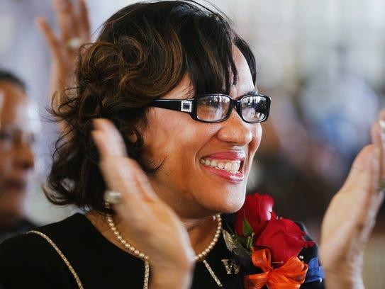 Newly sworn in Flint Mayor Dr. Karen Weaver claps during