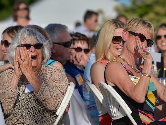Sunglasses-equipped spectators applaud for the dancers under sunny skies Monday night.