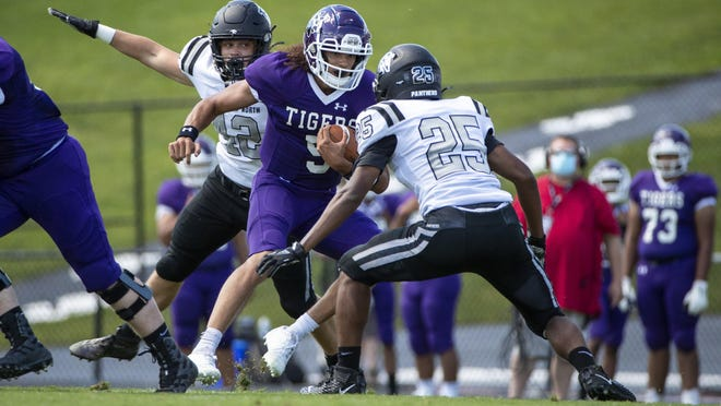Pickerington Central's Garner Wallace, making his first start at quarterback for the Tigers, rushes upfield toward Pickerington North's Malik Ray. Wallace ran for 104 yards and a touchdown on 15 carries.