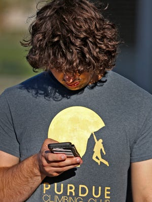 Ryan Baker checks his phone while waiting in line for eclipse glasses, at the Hamilton East Public Library in Fishers, Friday, August 18, 2017.  A limited number of glasses to view the solar eclipse were handed out at the library in preparation for Monday, August 21, 2017's event.  Many stood in line, but unfortunately many didn't get glasses.