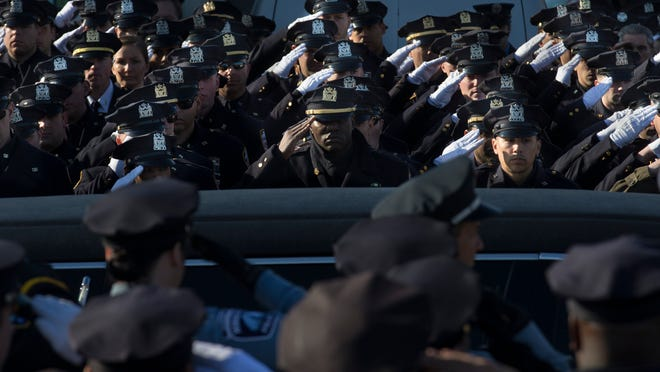 Police officers salute as the hearse of New York city Police Officer Rafael Ramos drives along his funeral procession route in the Glendale section of Queens on Saturday. Ramos and his partner, Officer Wenjian Liu, were killed Dec. 20 as they sat in their patrol car in Brooklyn.