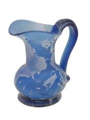 A pitcher blown from blue bottle glass, dating from early to mid-19th century.
