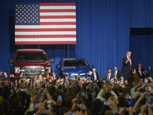 President Donald Trump waves to the auto industry crowd