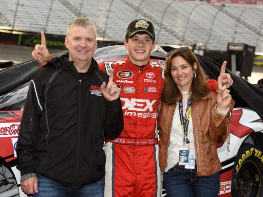 Harrison Burton, center, celebrates with his father, Jeff Burton, left, and mother, Kim Burton, after winning a NASCAR K&N Pro Series East race at Bristol Motor Speedway on April 22.