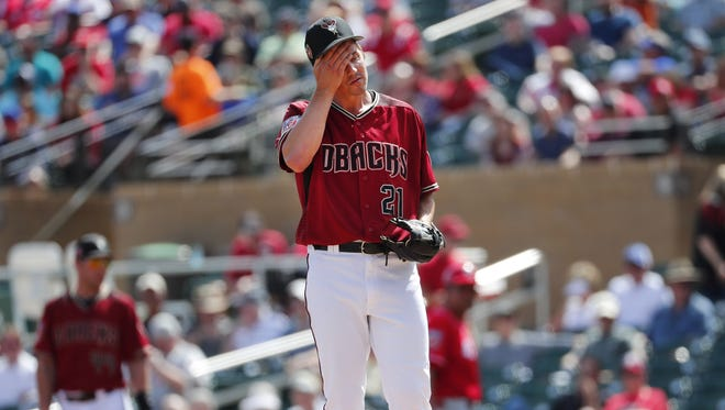 Arizona Diamondbacks starting pitcher Zack Greinke (21) wipes his head during a spring training game against the Cincinnati Reds at Salt River Fields at Talking Stick. March 14, 2018.