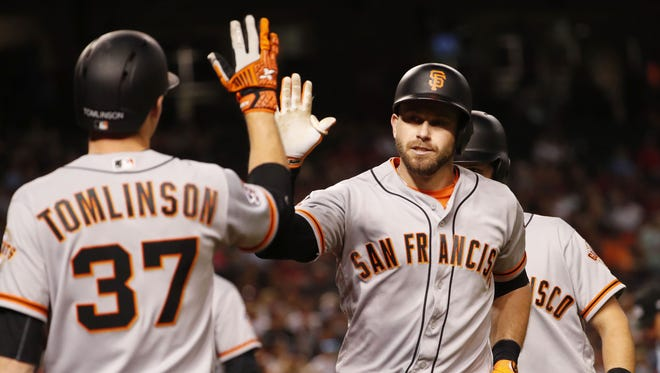 San Francisco Giants' Evan Longoria (10) slaps hands with Kelby Tomlinson (37) after hitting a two-run home run against Arizona Diamondbacks pitcher Robbie Ray (38) during the sixth inning at Chase Field April 18, 2018.