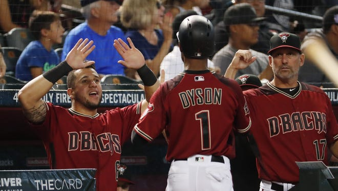 Arizona Diamondbacks center fielder Jarrod Dyson (1) is congratulated by left fielder David Peralta (6) and manager Torey Lovullo after scoring against the Miami Marlins during the seventh inning at Chase Field in Phoenix June 3, 2018.