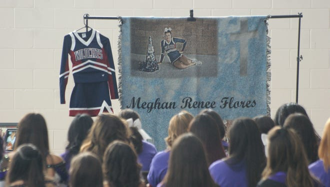 Cheerleaders from Deming High School and Deming Dust Devils are seated at a memorial for Meghan Renee Flores, whose uniform was on display.