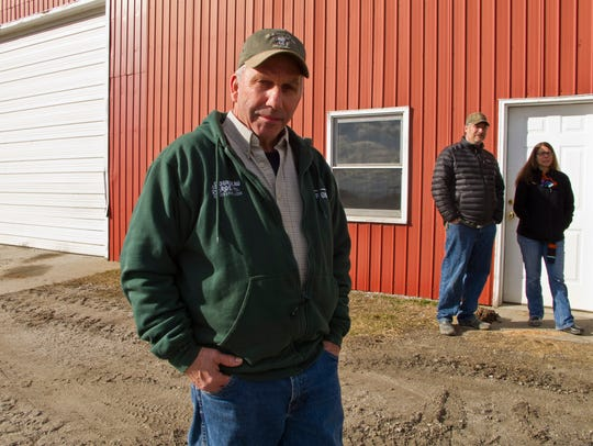 Wayne Fiske, at left, stands outside the shop at his
