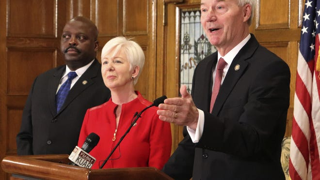 Gov. Asa Hutchinson speaks at a news conference Monday at the state Capitol in Little Rock, with Daryl Bassett, the head of Arkansas' Department of Workforce Services, and Cindy Gillespie, the director of the state Department of Human Services. The federal Centers for Medicare and Medicaid Services on Monday approved a state plan to require that thousands of people on its Medicaid expansion seek ways to work or volunteer. Traditional Medicaid recipients are not affected. Arkansas is the third state to win permission, following Kentucky and Indiana.