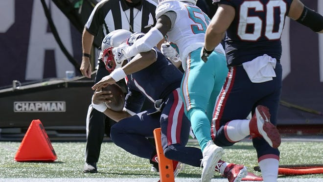 New England Patriots quarterback Cam Newton (1) scores his second rushing touchdown as Miami Dolphins linebacker Jerome Baker (55) chases in the second half of an NFL football game, Sunday, Sept. 13, 2020, in Foxborough, Mass.
