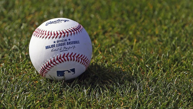 A baseball finds the grass at the Cincinnati Reds baseball spring training facility Friday, Feb. 17, 2017, in Goodyear, Ariz.