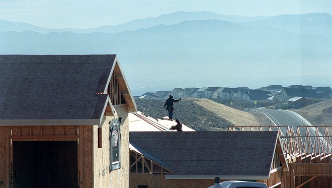 File photo: Workers construct homes in northwest Reno.