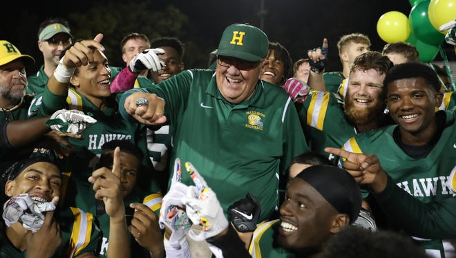 Farmington Hills Harrison coach John Herrington celebrates his team's 39-0 win over Berkley, allowing Herrington to set the record for most wins in state history Oct. 13, 2017, at Harrison.