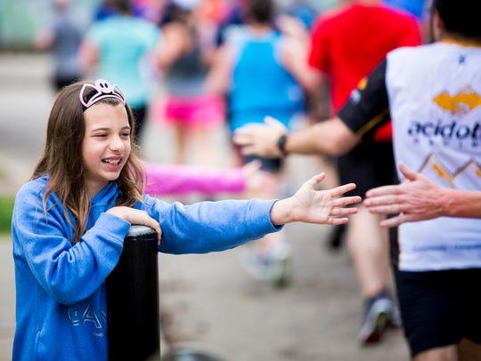 Gracie Dames, 10, of Edgewood, Ky., cheers on runners