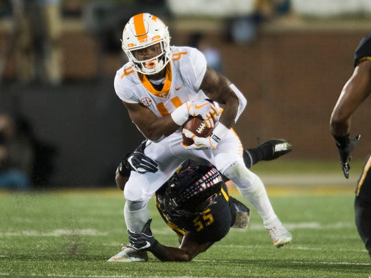 Tennessee running back John Kelly (4) attempts to stay on his feet as Missouri defensive lineman Jordan Harold (55) tries to take him down during a game between Tennessee and Missouri at Faurot Field in Columbia, Missouri, on Saturday November 11, 2017.
