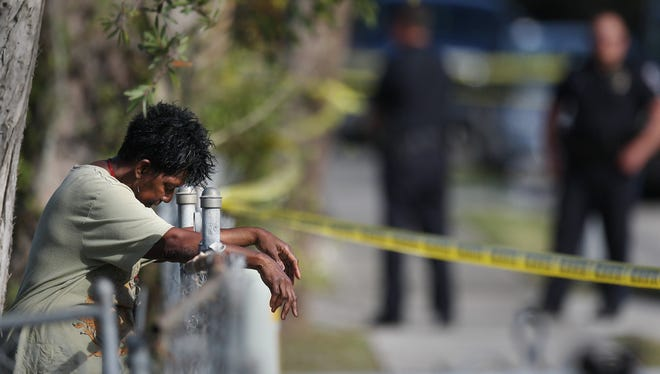 """Jerri Rockett bows in prayer Saturday (1/24/15) after her nephew Malcolm Huggins was killed in a shooting in Fort Myers. """"I prayed for peace and calm."""""""