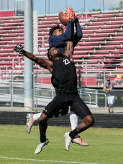 Taejon Wright of Naples High School makes a catch over South Fort Myers defender Eddie Teague in the 7-on-7 football tournament on Wednesday at South Fort Myers High School.