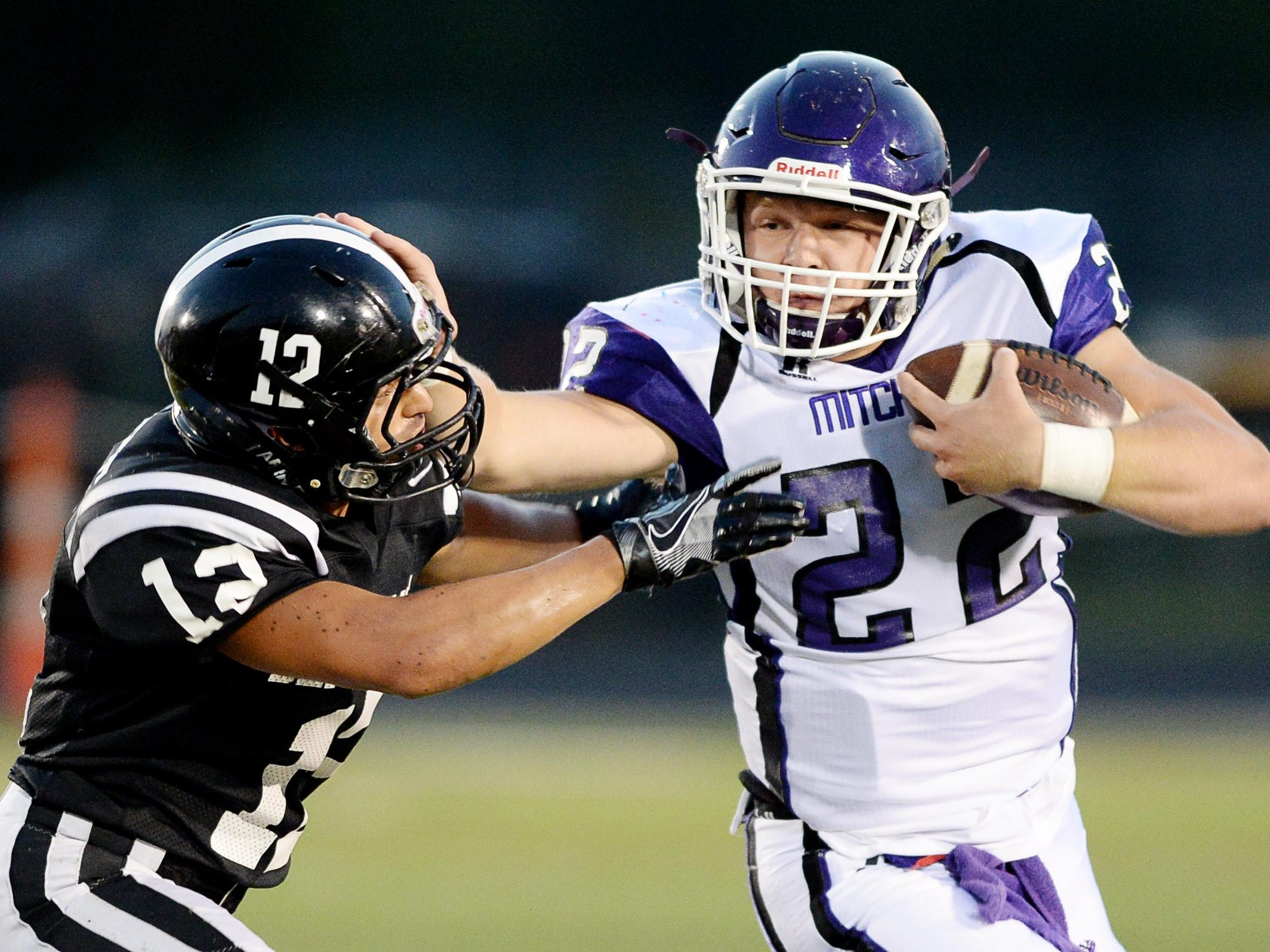 Mitchell's Ben Young, right, stiff-arms North Buncombe's Nick Lisenbee on Friday in Weaverville.
