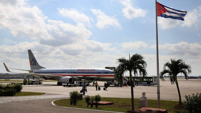 Passengers walk across the tarmac at Jose Marti International Airport after arriving on a charter plane operated by American Airlines January 19, 2015 in Havana.