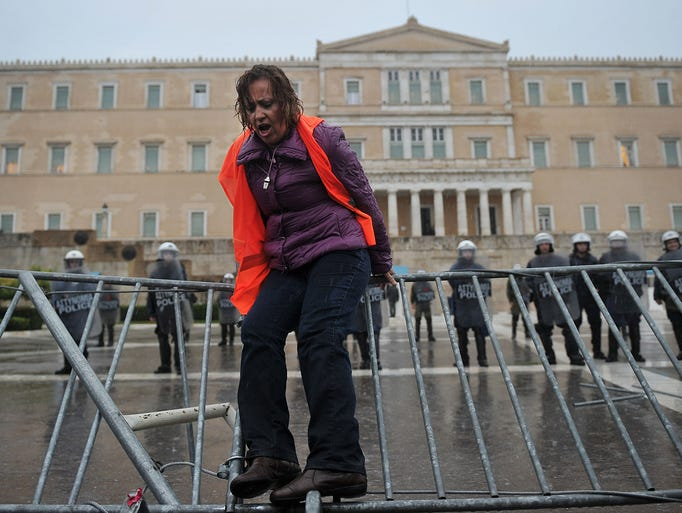 A laid-off school guard jumps over a barrier protecting the Greek parliament building during a demonstration on Nov. 6 in Athens. A general strike against further austerity cuts has paralyzed public services and disrupted transportation.